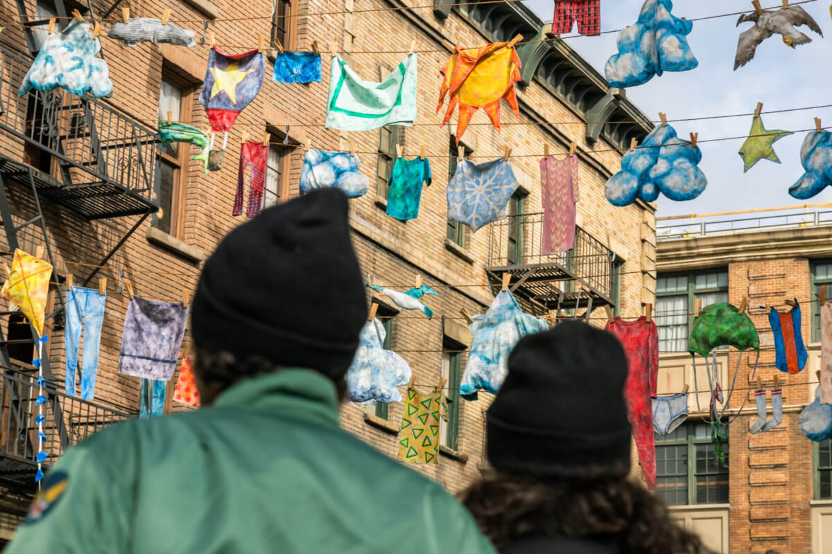 People looking up at artwork hanging from clothes lines